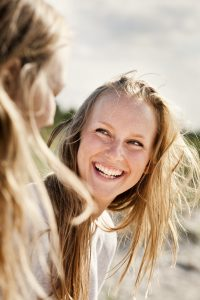Cheerful woman looking at friend at beach against sky