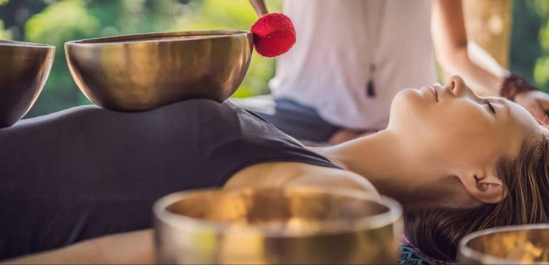 Woman experiencing sound therapy from bowl