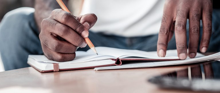 Close up of man writing goals in his notebook